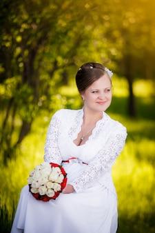 Braut, die mit blumen auf dem gras im park sitzt.