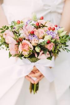 Braut, die rosenblumenstrauß, abschluss hochhält