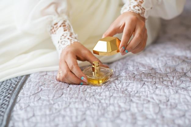Braut, die sanftes parfüm auf ihr handgelenk aufträgt