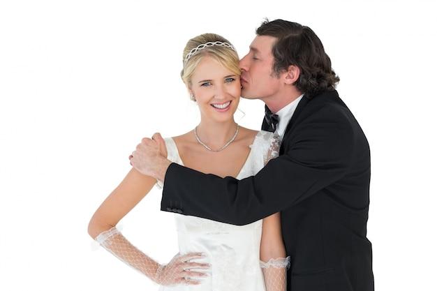 Braut, die vom bräutigam geküsst wird