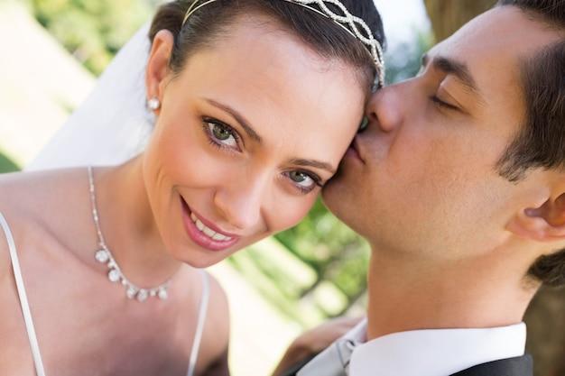 Braut, die vom bräutigam im garten geküsst wird