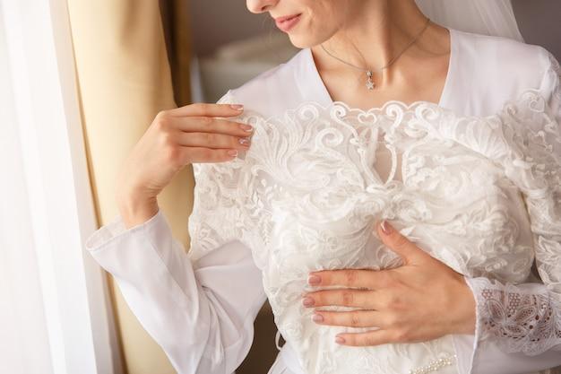 Braut, die weißes hochzeitskleid mit spitze hält