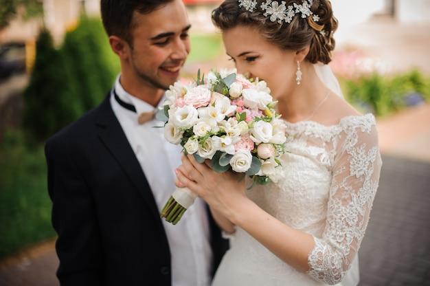 Braut genießt den duft eines hochzeitsstraußes, der bräutigam steht neben dem lächeln