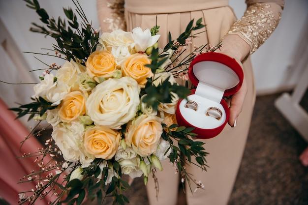 Braut hält blumenstrauß und eheringe