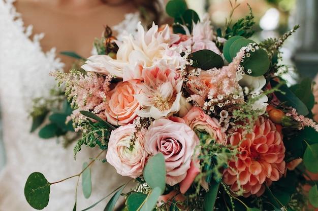 Braut hält den reichen hochzeitsblumenstrauß, der von den orange und roten herbstblumen gemacht wird
