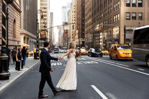 Braut hält die hand des bräutigams, die über die straße in new york geht