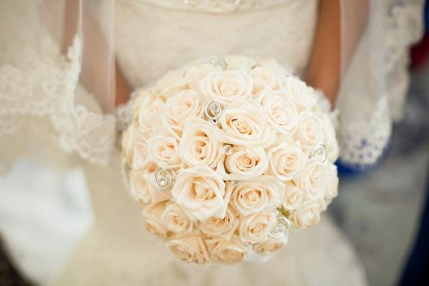 Braut hält einen ausgezeichneten hochzeitsblumenstrauß, der von den creme-rosen ein gemacht wird