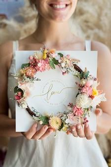 Braut hält einen blumenkranz mit einer hochzeitseinladung