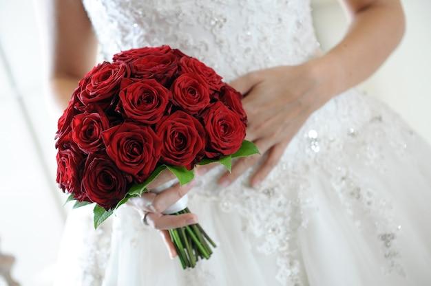 Braut hält einen blumenstrauß aus tiefroten rosen, die ewige liebe symbolisieren, in einer nahaufnahme auf ihrer hand vor ihrem brautkleid