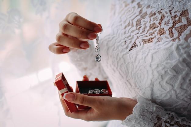 Braut hält einen ohrring