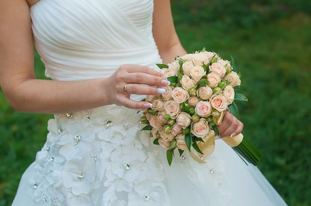 Braut hält einen schönen hochzeitsblumenstrauß