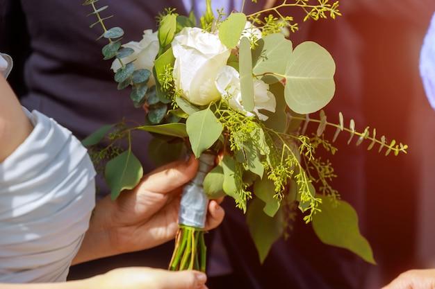 Braut hält eleganzstrauß mit blättern und rosen