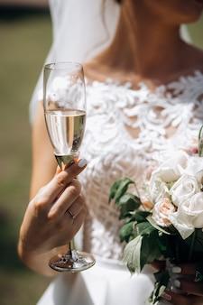Braut hält glas champagner und einen hochzeitsblumenstrauß draußen