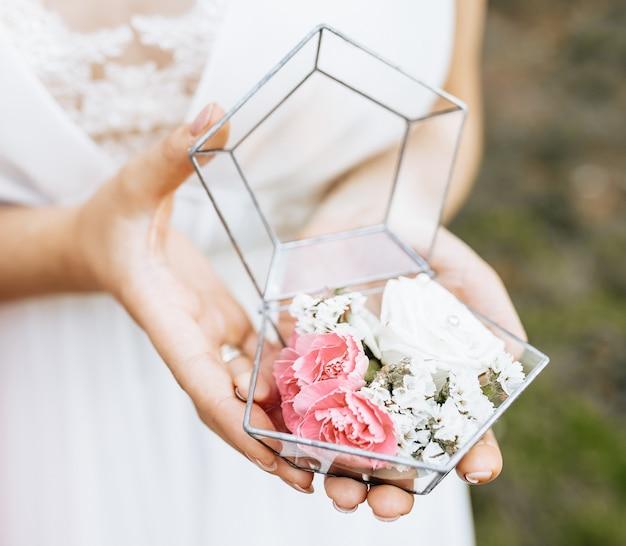 Braut hält hochzeitsbox für ringe mit weißen und rosa blumen