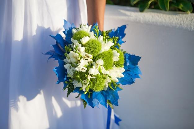 Braut hält hochzeitsstrauß in den weißen und grünen farben und im blauen dekor.