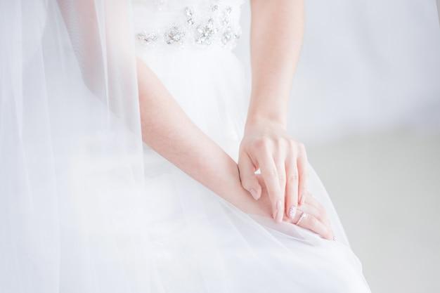 Braut hält ihre hände auf den knien gekreuzt