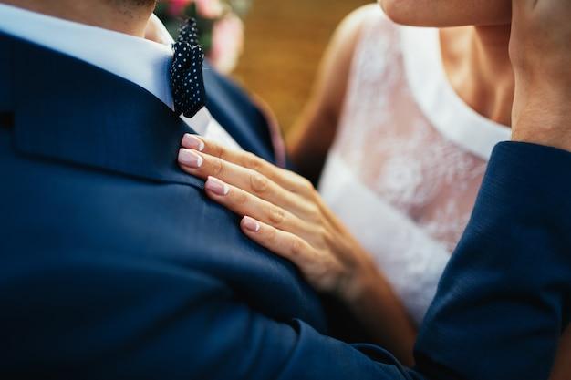 Braut hält ihre hand auf die brust des bräutigams