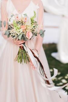 Braut hält in ihren händen reichen blumenstrauß mit langen streifen