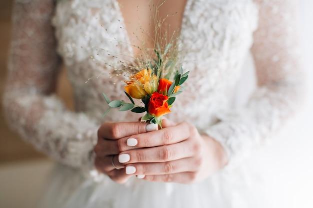 Braut hält knopfloch mit beiden händen