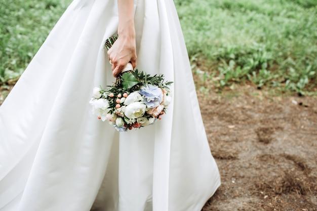 Braut hält luxuriösen brautstrauß mit hortensien und pfingstrosenrosen