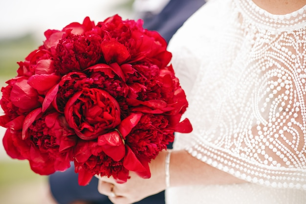 Braut hält reichen hochzeitsblumenstrauß gemacht von den roten pfingstrosen