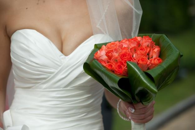 Braut hält roten hochzeitsblumenstrauß hinter ihrer verlockenden truhe