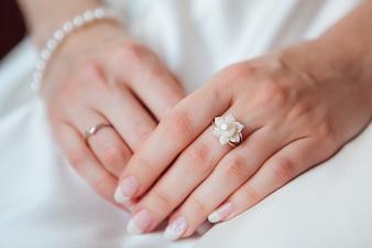 Braut Hand mit Diamantring und Perlenarmband auf weißem Kleid