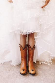 Braut hebt ihren rock, um die stiefel darunter zu zeigen