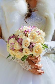 Braut im designerkleid, das einen rosenblumenstrauß hält.