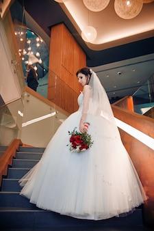 Braut im eleganten hochzeitskleid, das auf treppen steht