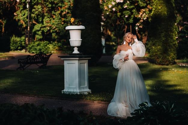 Braut im garten, morgen und braut, brautgebühren, morgenbraut, weißes kleid, ohrringe tragen.