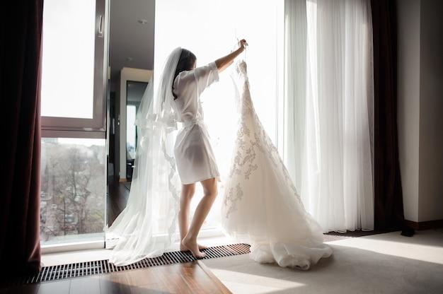 Braut im hausmantel und schleier, die hochzeitskleid auf einem aufhänger halten
