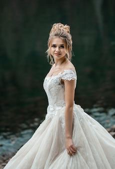 Braut im hellen chiffonhochzeitskleid, das nahe den bergen aufwirft