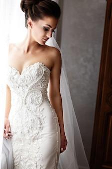 Braut im herrlichen hochzeitskleid mit crystls und perlen steht vor hellem fenster