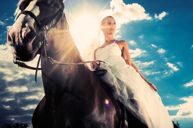 Braut im hochzeitskleid, das ein pferd, hintergrundbeleuchtet reitet