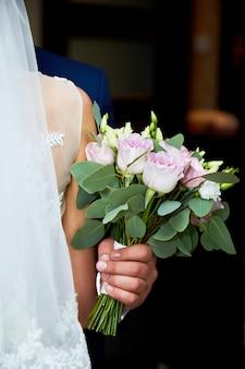 Braut im hochzeitskleid und bräutigam mit einem blumenstrauß und grüns in den händen.