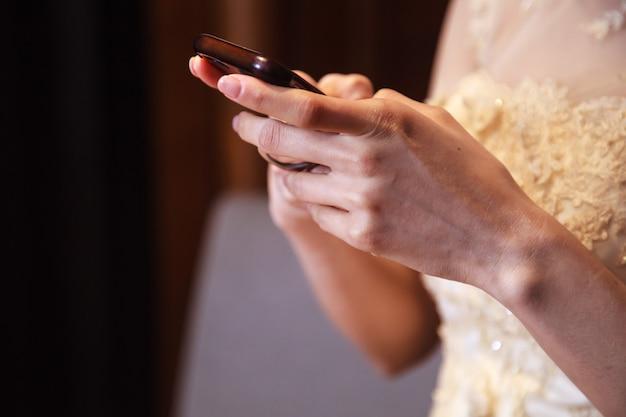 Braut im hochzeitskleid unter verwendung des intelligenten handys, einkaufen und kommunikation mit digitaler technologie