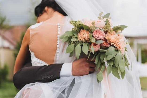Braut im kleid des offenen rückens, das ihren bräutigam umarmt, der einen hochzeitsblumenstrauß draußen hält