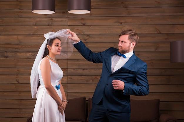 Braut im kleid und schleier gegen bräutigam im anzug