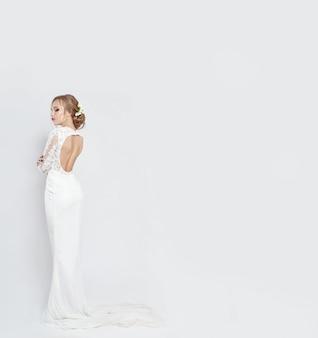 Braut im langen weißen hochzeitskleid auf einem weiß. luxuriöses kleid
