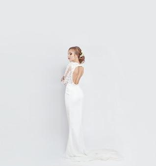 Braut im langen weißen hochzeitskleid auf einem weiß