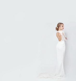 Braut im langen weißen hochzeitskleid auf weißem hintergrund. luxuriöses kleid im körper einer frau. das mädchen bereitet sich auf die heirat vor. perfekte figur und kleidung frauen