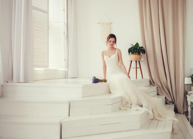 Braut im schönen kleid, das zuhause auf sofa sitzt