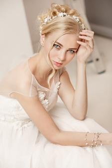 Braut im schönen kleid steht drinnen im weißen studio-interieur wie zu hause.