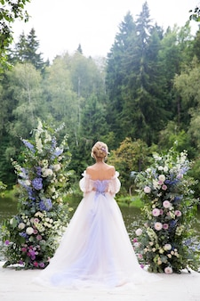 Braut im schönen weißen kleid, das auf der küste des flusses in einem wald bleibt