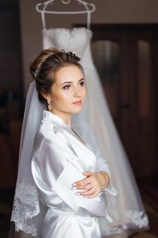 Braut im weißen bademantel mit make-up und brautschleier verschränkten armen