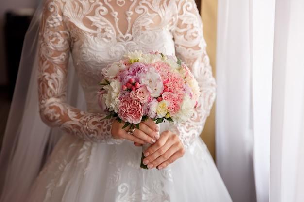 Braut im weißen hochzeitskleid, das hochzeitsstrauß hält