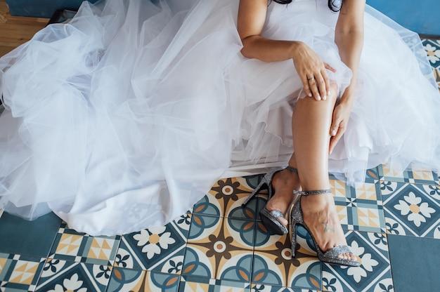 Braut im weißen hochzeitskleid, das silberne schuhe anzieht.