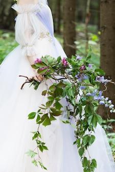 Braut im weißen kleid, das großen hochzeitsblumenstrauß von blumen im wald hält