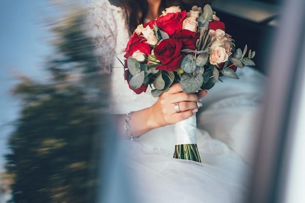 Braut im weißen kleid, das hochzeitsblumenstrauß von roten rosen hält